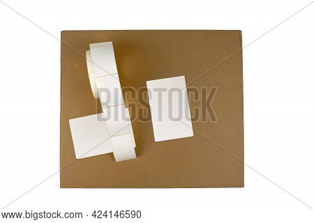 Stickers On A Cardboard Box, Top View, Isolate On A White Background. Label Reel For Printers. Label