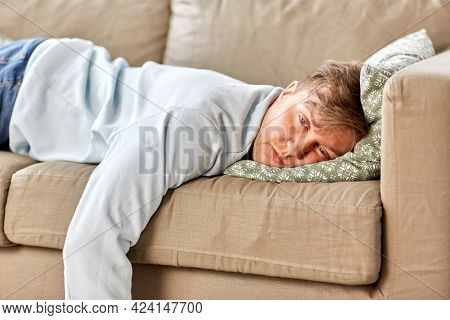 people, boredom and depression concept - bored or lazy young man lying on sofa at home