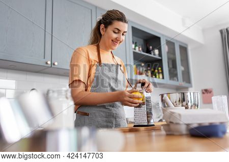 culinary, baking and people concept - happy smiling young woman cooking food on kitchen at home and grating lemon peel on grater