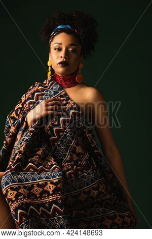 African American Woman In Colorful Headscarf, Earrings And Necklace Sitting Wrapped In Ornament Blan