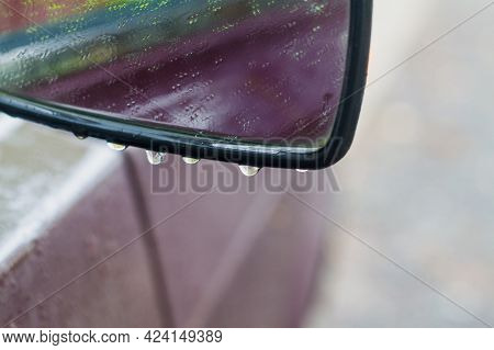 Car Side Mirror In The Rain In Water Drops.