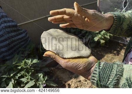 Woman Making Indian Or Pakistani Flatbread Made Of Pearl Millet Known As Bajre Ki Roti. Dough Is Fla