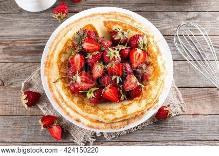 Pancakes With Strawberries Close-up. Maslenitsa. Thin Freshly Baked Pancakes With Strawberries. Dess