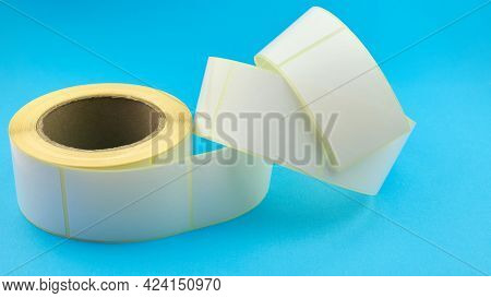 Babina Of Self-adhesive Stickers On A Blue Background. White Roll Of Labels For Thermal Perforation