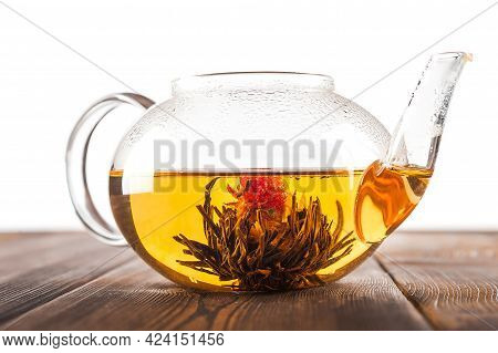 Bound Tea In Transparent Teapot On Wooden Background.