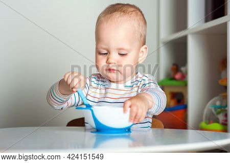 Handsome Toddler Sitting With Plate Close-up. Baby Complementary Feeding, Food Allergy, Intolerance