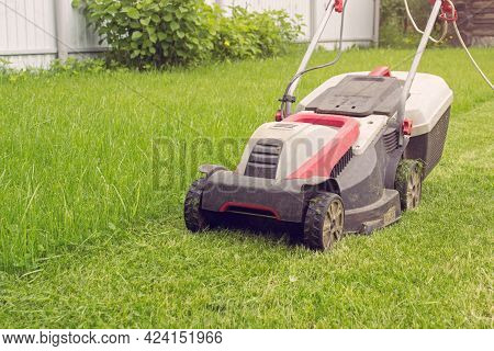 A Lawn Mower On A Lush Green. Details Of Landscaping And Gardening