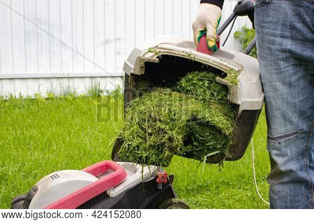 Man With Lawn Mower Grass Collector In Hand. Man With Lawnmower. Gardening And Landscaping Concept