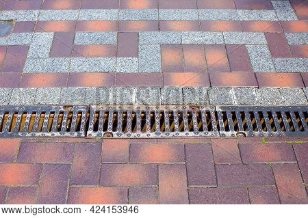 Iron Grating Line Of The Drainage System Of The Pedestrian Sidewalk Made Of Stone Tiles Improvement