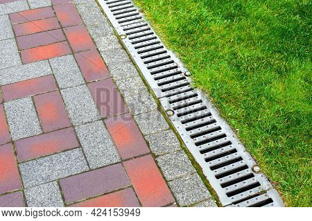Iron Grating Line Of The Drainage System Of The Pedestrian Sidewalk Made Of Stone Tiles Landscaping