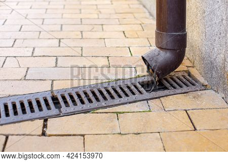 Pvc Downpipe Rainwater System With A Drainage Grate On A Stone Tile Sidewalk And A House With A Pipe