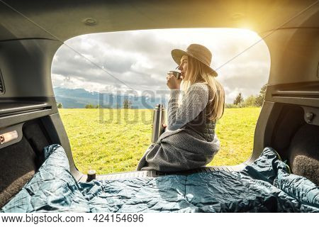 Girl resting in her car. Woman hiker, backpacker traveler camper in sleeping bag, relaxing, drinking hot tea on top of mountain. Road trip. Health care, authenticity, sense of balance and calmness.