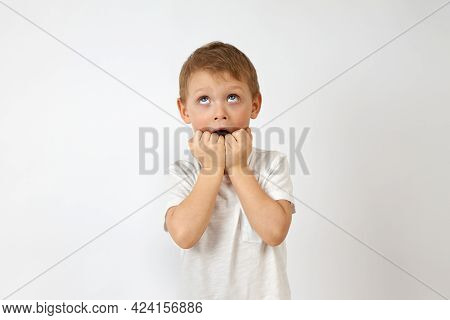 Child With Horror Looks Up Biting His Hands In Fear On A White Background. Emotion Of Fear On The Fa