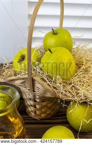 Green Apples, Basket With Apples And Jug With Apple Juice On Wooden Background