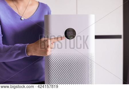 Woman Hands Pointing To Screen Of White Modern Air Purifier In A Living Room For Refresh Air Flow At