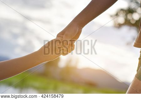 Hands Of Two Child Holding Each Other On Nature Background. Concept Of Mutual Assistance And Friends