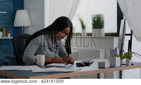 Black Student Writing Education Ideas On Stickey Notes Sitting At Desk Table In Living Room. Young W