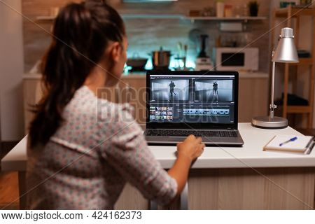 Back View Of Creative Filmmaker Working On A Movie On Laptop During Midnight. Content Creator In Hom