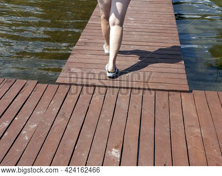 Bare Female Legs Walking Down A Timber Pier Toward A Water, Outdoor Cropped Shot