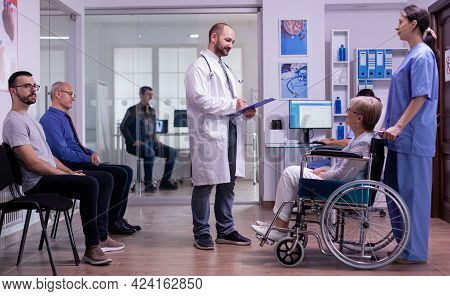 Medic Talking With Disabled Woman In Hospital Waiting Area, Reading Registration Form From Clipboard