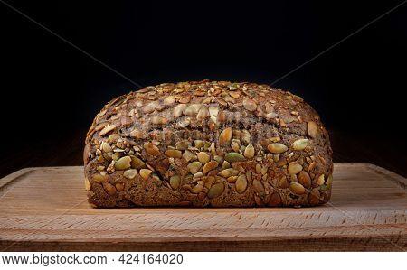 A Bread Bun With Pumpkin Seeds On A Wooden Board.