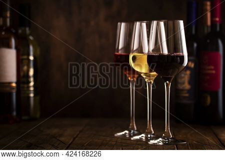 Wine Tasting. Red, White And Rose Wine In Glasses On Wooden Background In Rustic Cellar Or Bar With