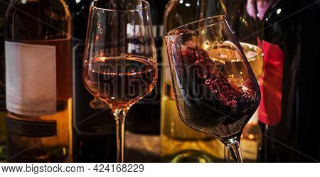 Wine Tasting. Red Wine Shaking In Glass On Background With Selection Of Red, White And Rose Wines In