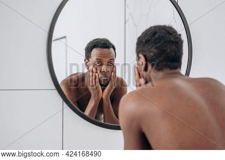 Young African-american Man With Bare Torso Reflection Looking In Round Mirror Making Face In Spaciou