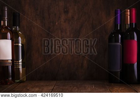 Wine Tasting. Red, White And Rose Wines On Wooden Background In Rustic Cellar Or Bar With Collection