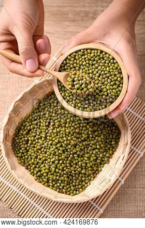 Mung Bean Seeds In Wooden Spoon And Bowl Holding By Hand, Food Ingredients In Asian Cuisine And Prod