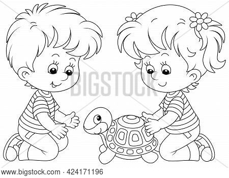Little Girl And Boy Friendly Smiling And Playing With Their Funny Small Turtle In A Nursery School,