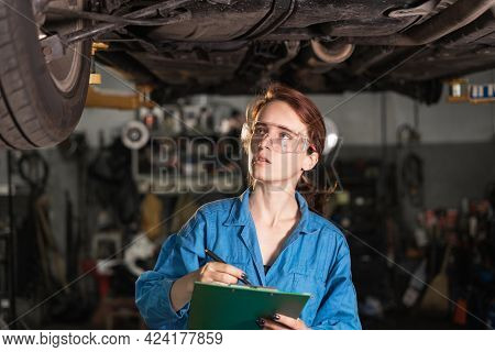 Portrait Of A Girl In Overalls And Glasses In A Car Repair Shop. Blue Overalls On A Woman Car Mechan