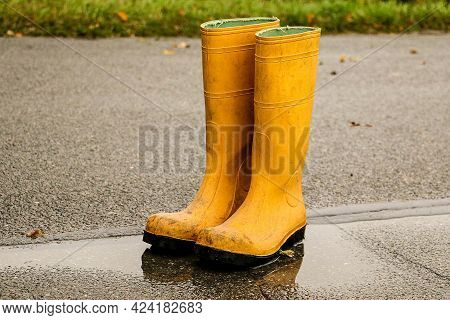 Old Yellow Rubber Boots Stand In A Puddle On The Street