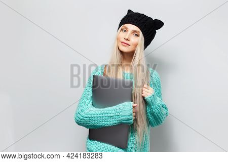 Portrait Of Blonde Happy Girl With Laptop In Hands On White Background. Wearing Black Hat And Cyan S