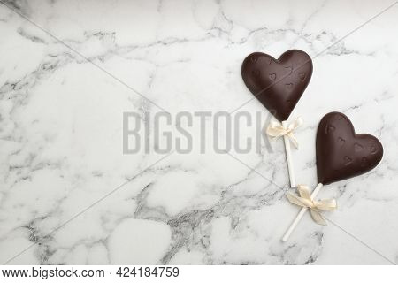 Chocolate Heart Shaped Lollipops On White Marble Table, Flat Lay. Space For Text