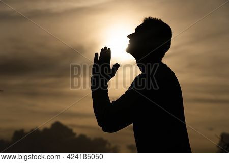 Silhouette Of Man Pray On During Sunset. Repentance, Regret And Hope Concept