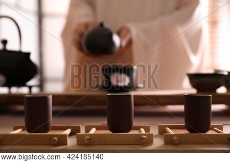 Master Conducting Traditional Tea Ceremony At Table Indoors, Focus On Cups