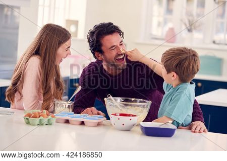 Children Putting Cake Mixture On Father's Nose In Kitchen As They Have Fun Baking Cakes Together