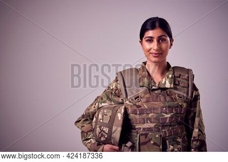 Studio Portrait Of Smiling Young Female Soldier In Military Uniform Against Plain Background