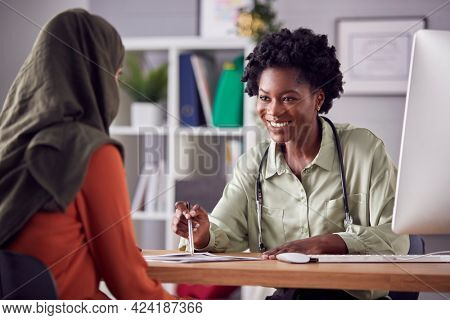 Female Doctor Or Consultant Having Meeting With Female Patient Wearing Headscarf To Discuss Scans