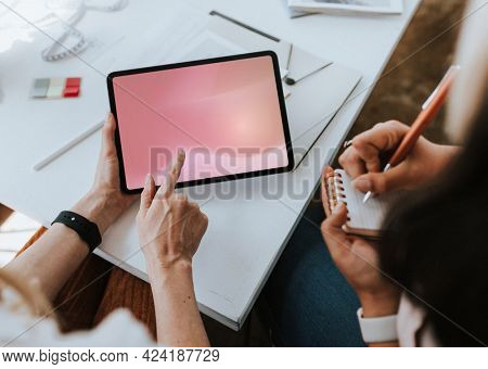 Fashion stylist taking notes from a digital tablet mockup