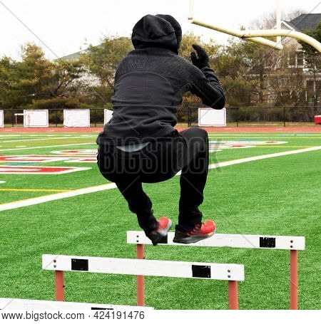 Am Athlete Is Jumping Over Track Hurdles On A Green Turf Field In The Winter Wearing A Hood And Glov