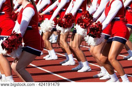 High School Cheerleaders In Red And White Uniforms Cheering To The Fans During A Football Game.