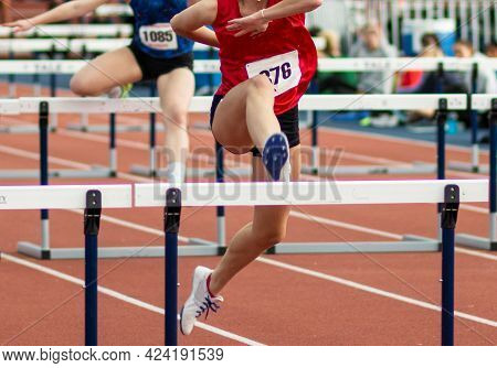 Two High School Girls Running In The Hurdles In An Indoor Track With Fans Sitting On The Side Watchi
