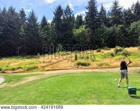 A Side View Of An Older Man Swinging A Golf Club On A Tee Box Surrounded By Forest Playing A Beautif