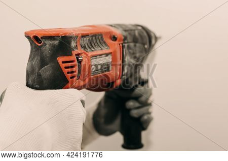 Electric Drill. Power Tools. The Hand Uses A Drill To Drill A Hole In The Wall. Repair. Construction
