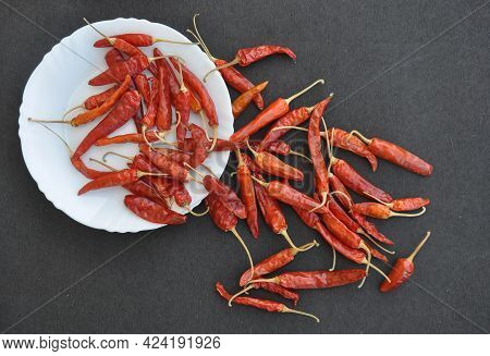Heap Of Red Chilli Peppers In White Plate With Spread On Rough Textured Black Color Table With Negat