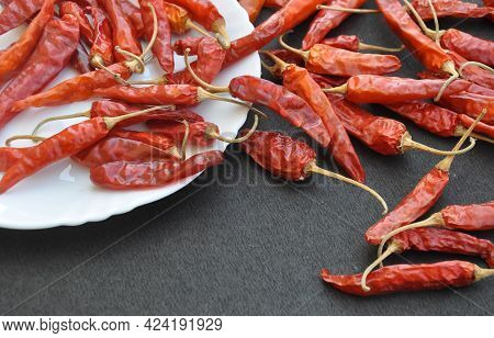 Close Up Of Red Chilli Peppers In White Plate With Spread On Rough Textured Black Table