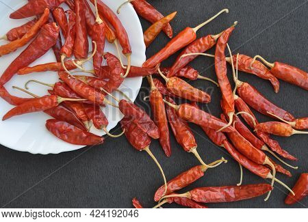 Overhead View Of Heap Of Red Chilli Peppers In White Plate With Spread On Rough Textured Black Table