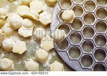 Raw Dumplings With Dumplings Maker On Table In Flour